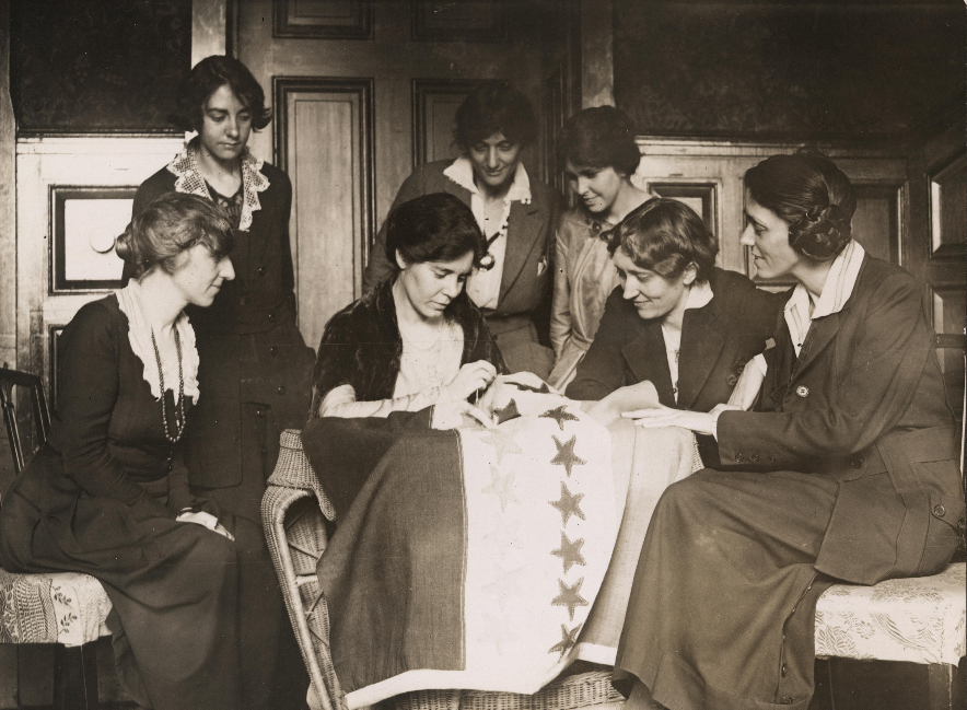 Alice Paul sewing a star on the suffrage flag