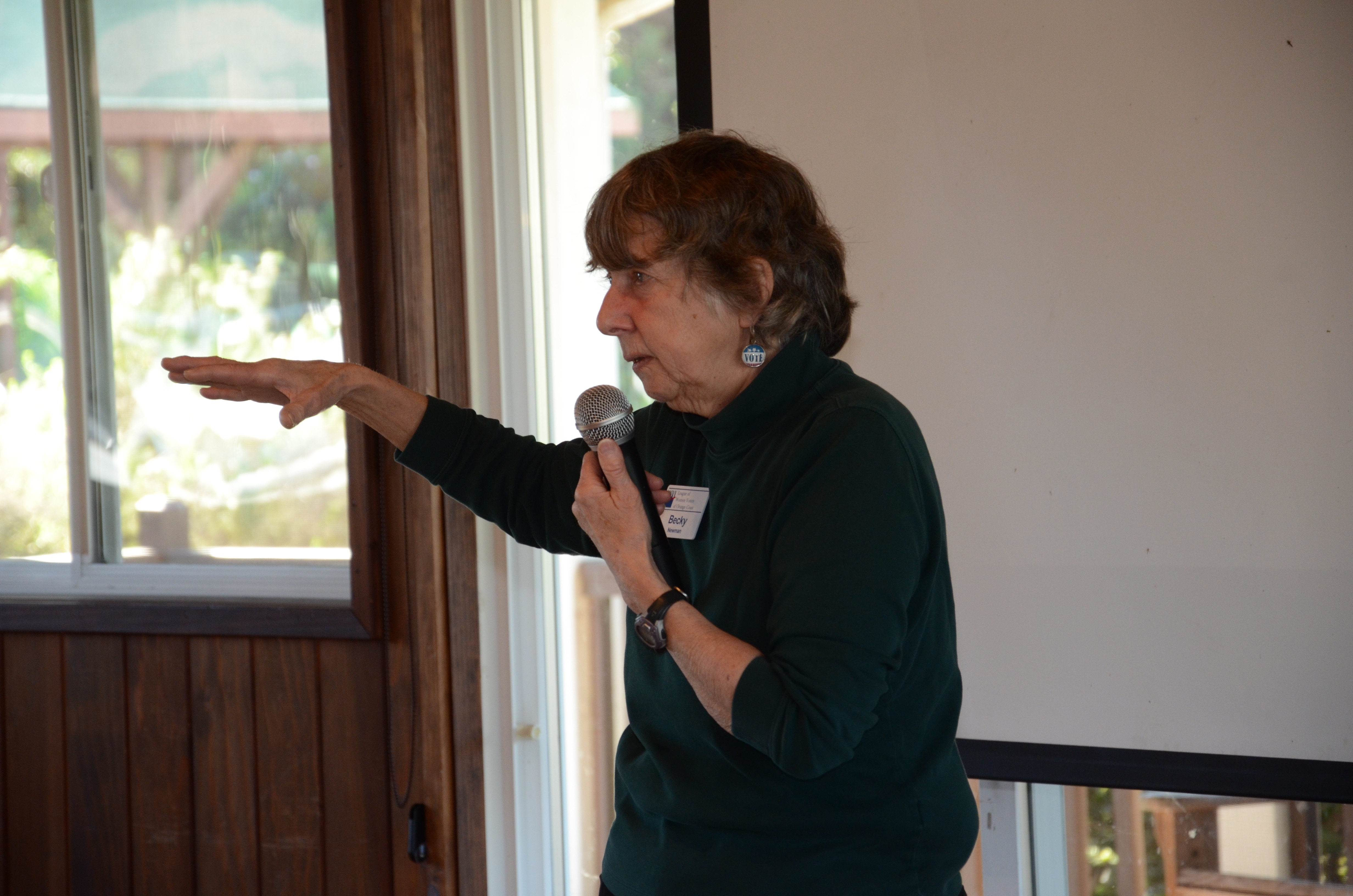 An image of a woman in a green sweater holding a microphone in one hand and gesturing with the other, which is lifted towards the audience with the palm down and the wrist bent.