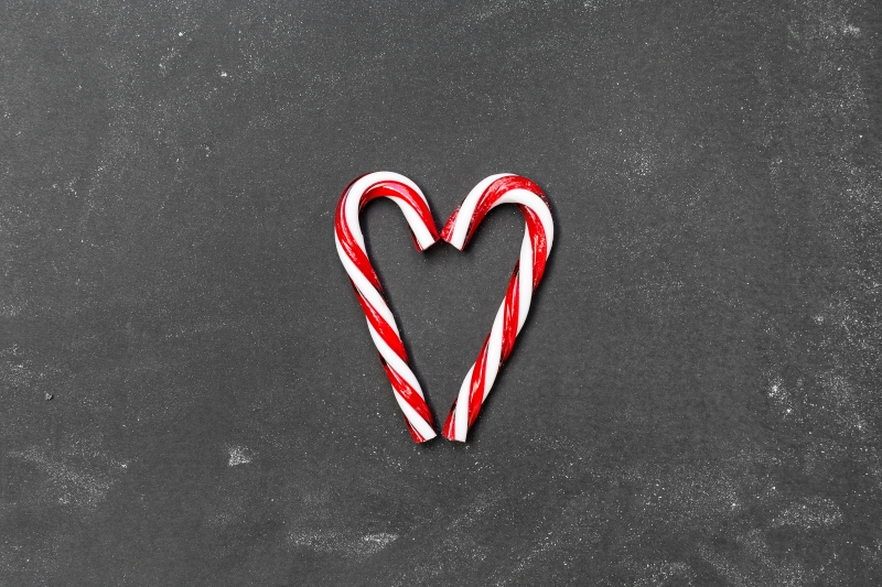 two red-and-white candy canes on gray surface forming a heart shape