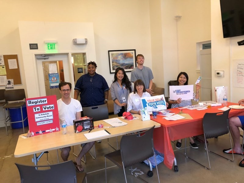 volunteers at table to help register voters