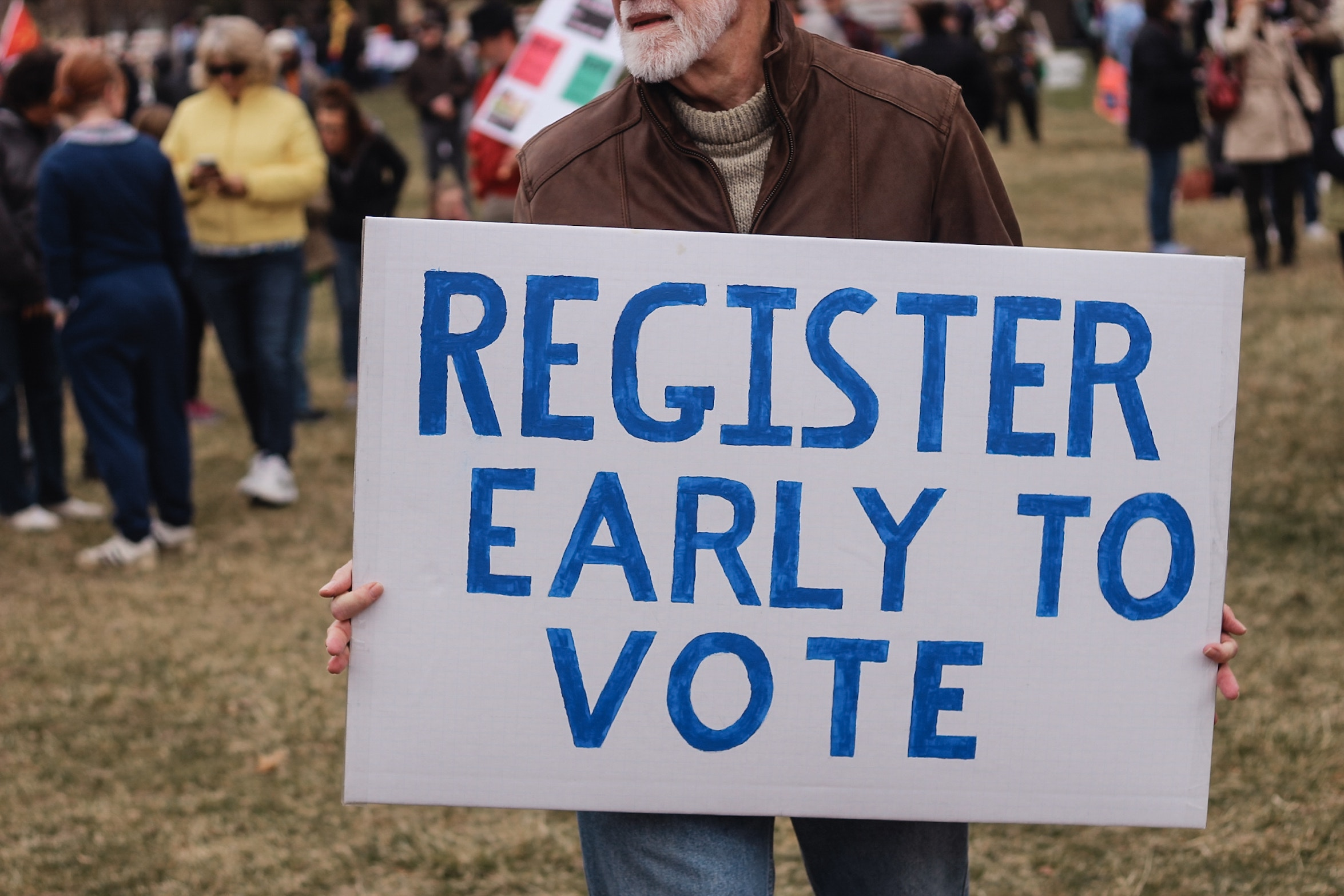 "Man holding a sign that reads ""Register Early to Vote"""