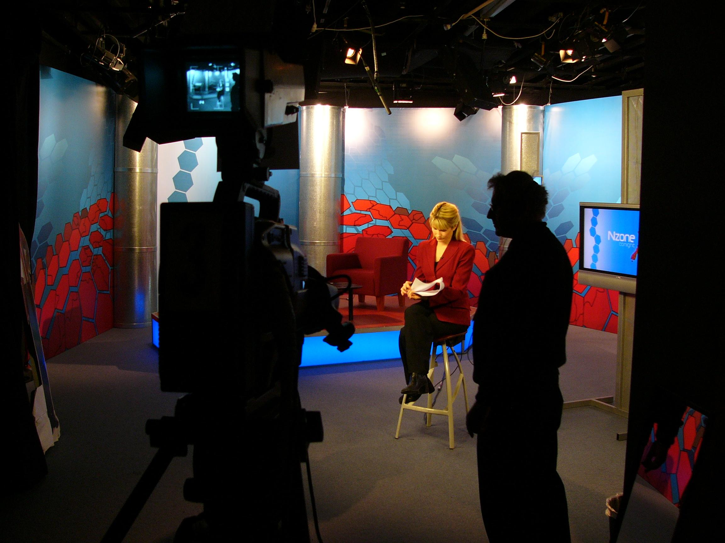 TV studio, cameramen in foreground with woman on stool in spotlight