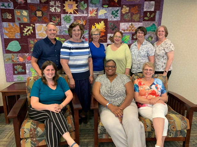 9 League board members standing in 2 rows, in front of a quilt, at the West Lafayette Public Library