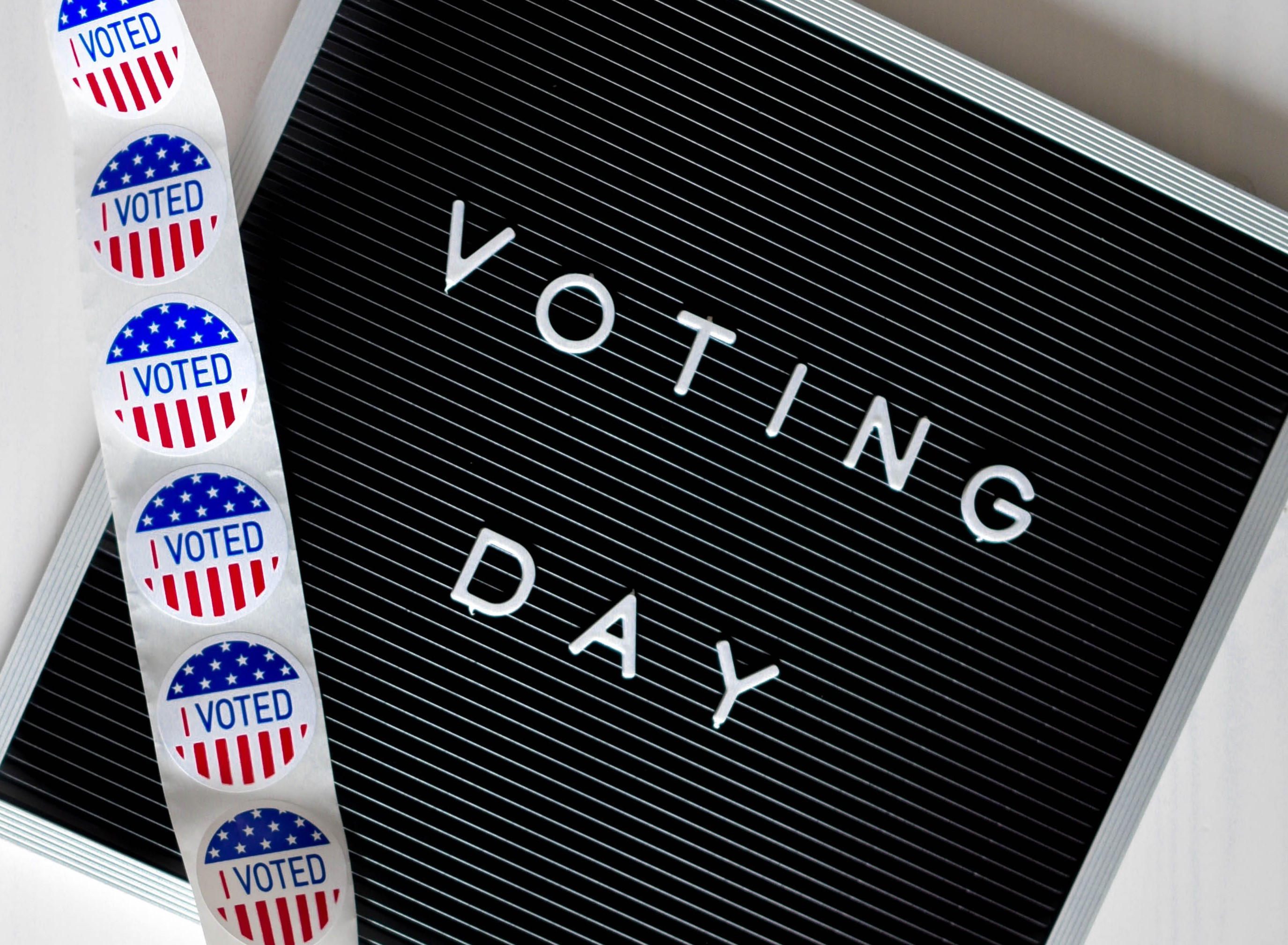 """Voting Day letterboard with strip of """"I VOTED"""" stickers draped over letterboard"""