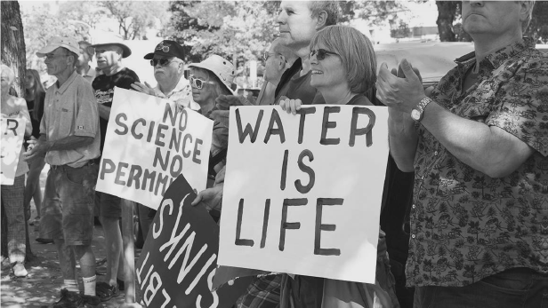 """People, protest sign reading """"Water is Life"""""""