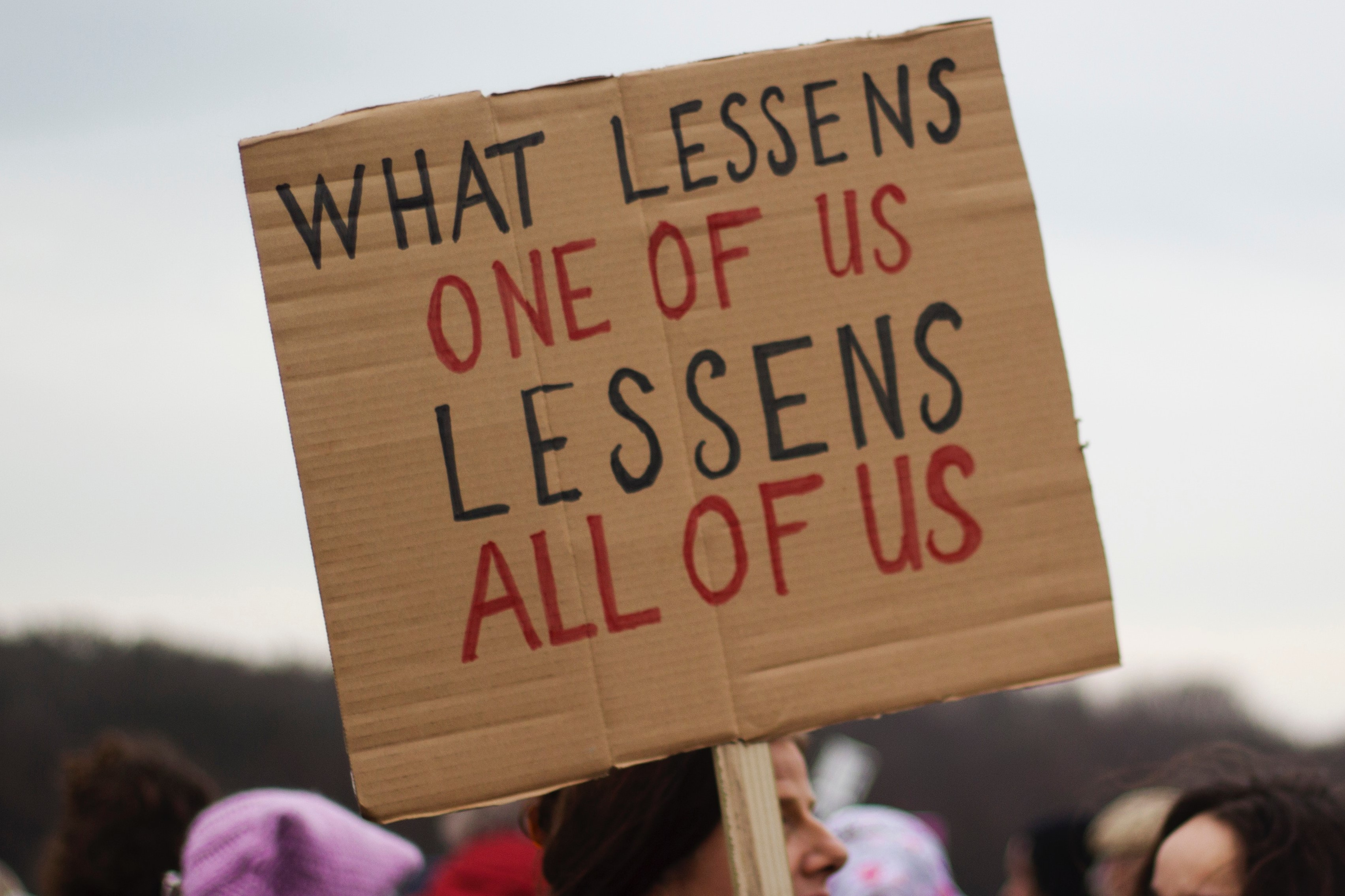 """Woman with sign that reads, """"What lessens one of us, lessens all of us."""""""