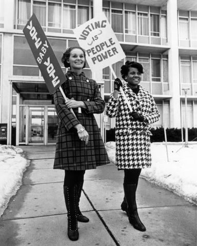 Two women in front of a building holding pro-voting signs