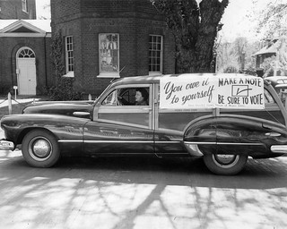 Historical Photo of a vintage car with voting signs