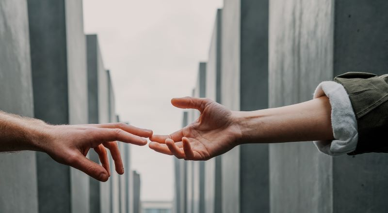 Photo of one person extending a hand to another