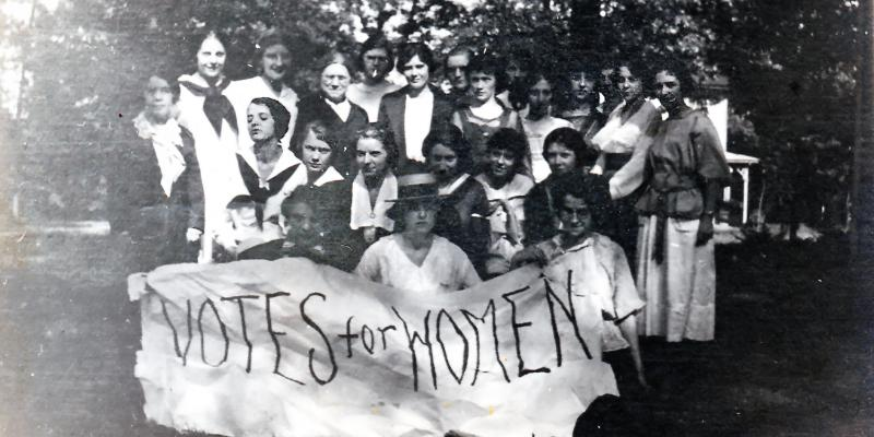 Group photo of Sufferagettes holding Votes For Women sign