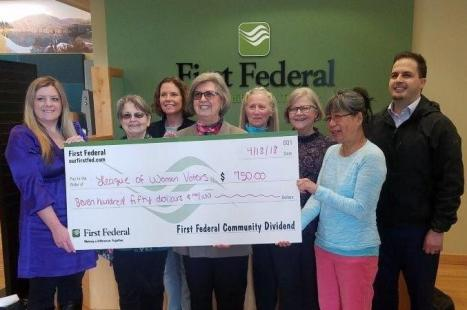 members and first federal reps around big check