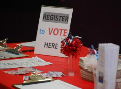 "Photo of Voter Registration Table with ""Register to Vote Here"" sign"