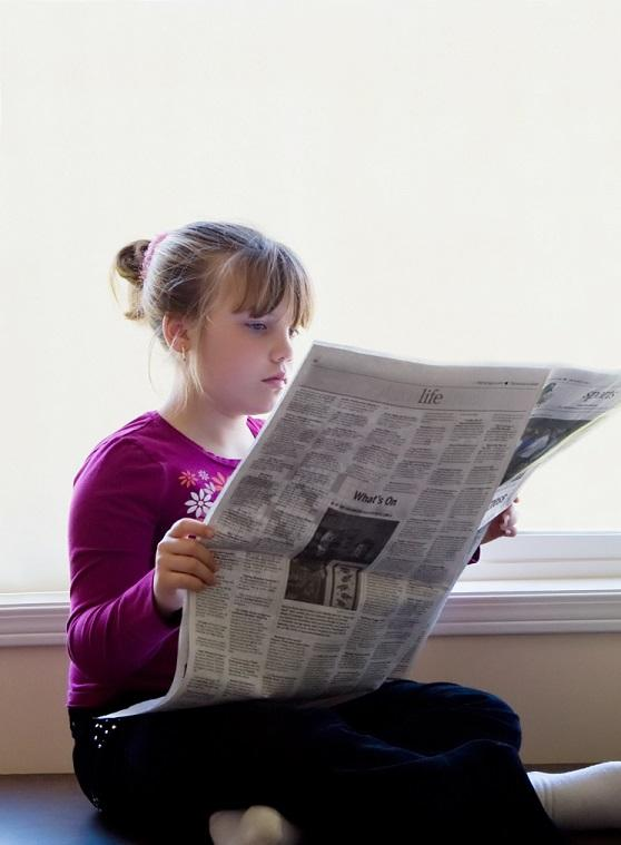 young girl reading newspaper