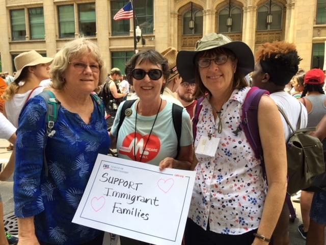 Three women with rally sign at march