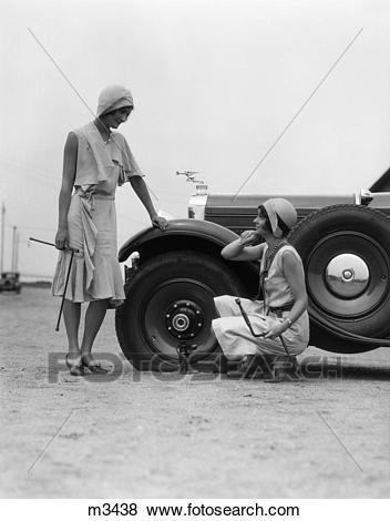 Photo of women from 1930s repairing car tire