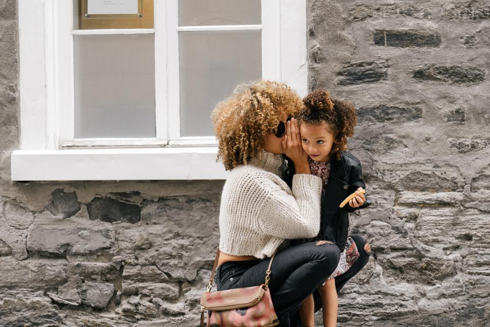 Photo of mother whispering to child