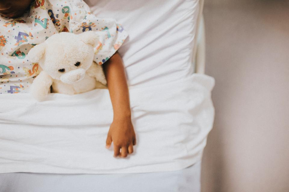Child in hospital bed with stuffed animal