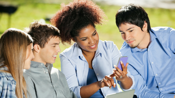Four students looking at a phone