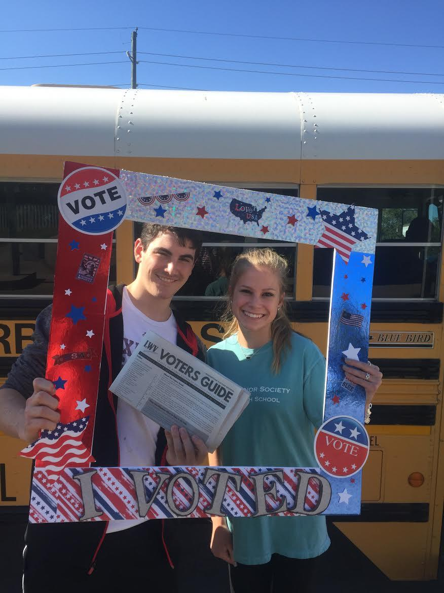 High School Voter Registration Cy-Fair with two students and a voters guide