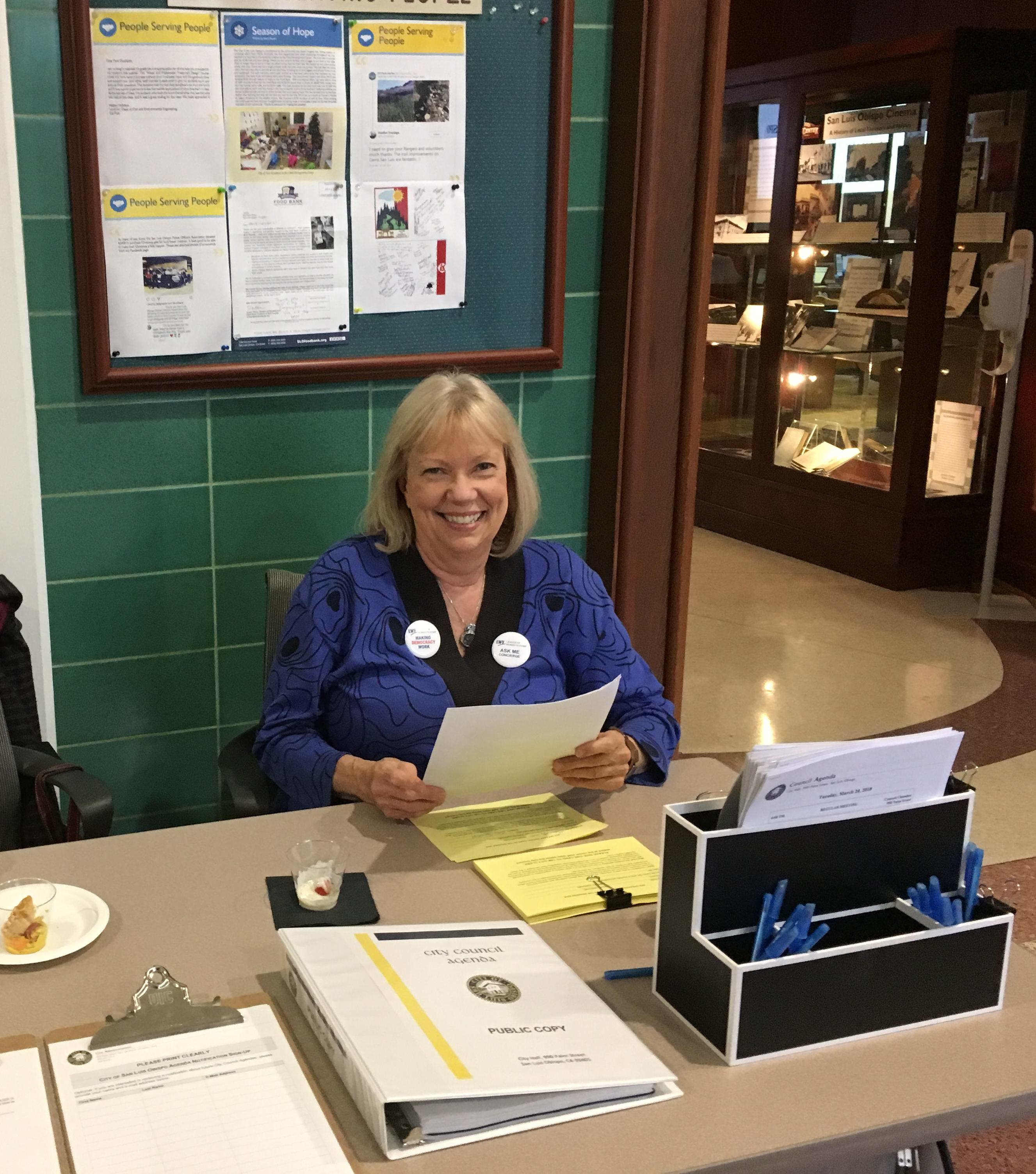 Sharon sits at table ready to assist the public
