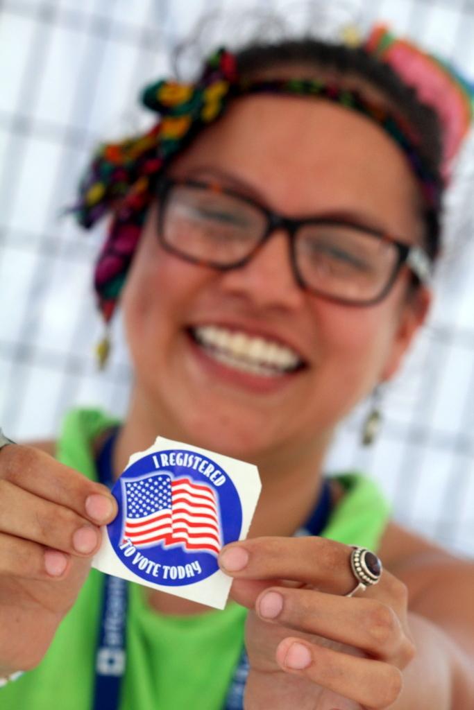 """smiling girl holding up  'I registered"""" sticker"""