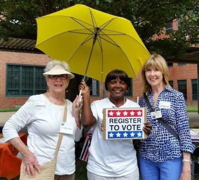 2 League members with registered voter, holding sign: Register to Vote