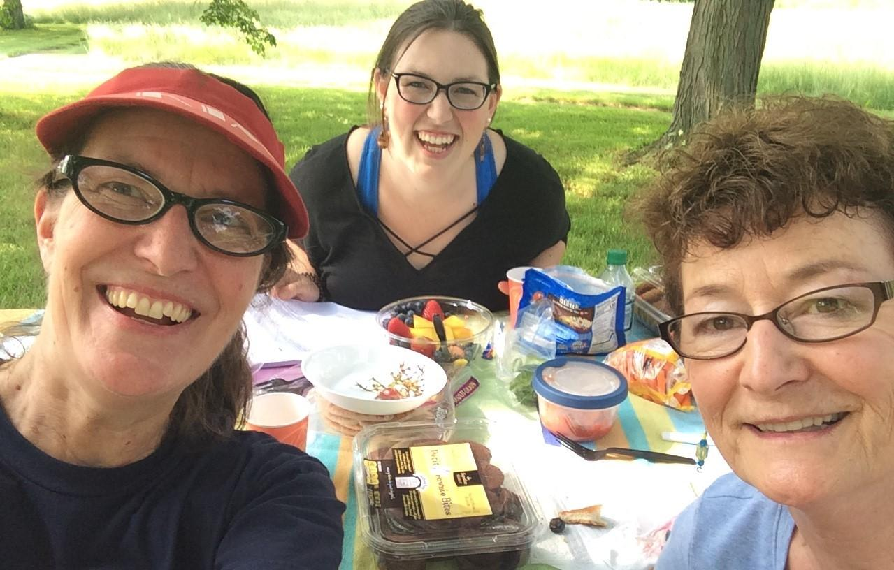 Three women at a picnic table in a grassy area, photo taken selfie-style