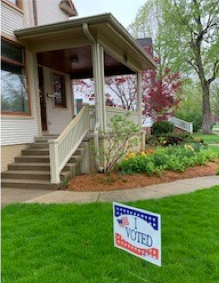 "A house with lawn has a ""I Voted"" sign out front."