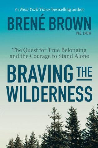 """An image of the cover of the book """"Braving the Wilderness"""" by Dr. Brené Brown. The title and author are printed in dark blue text over some evergreen treetops and a vast blue-gradient sky."""
