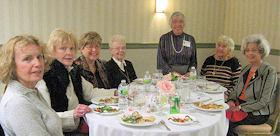 Julia Kayser and members sit around table at Winter Blahs Luncheon (Feb. 2011)