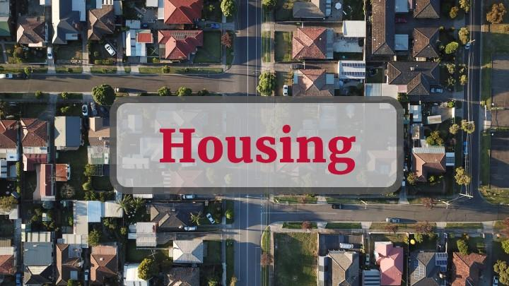 Housing - text overlay on stock photo of aerial view of homes in neighborhood