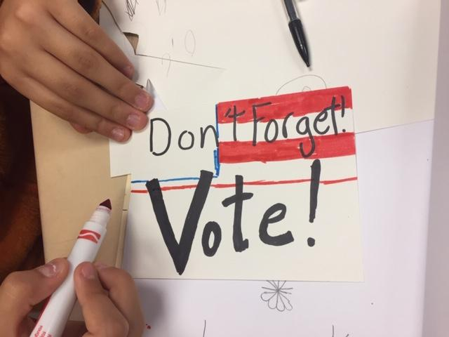 Photo of a student's hand as they make a reminder to vote postcard