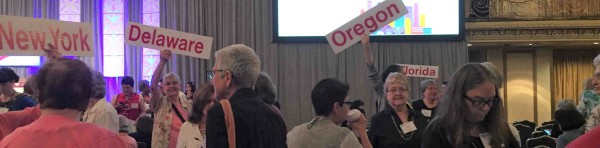 Placards with state names are held aloft amidst a convention crowd