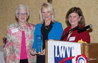 Three women near a podium with an LWV Banner