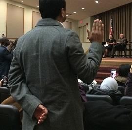 Man taking oath is shown from behind with his right hand raised