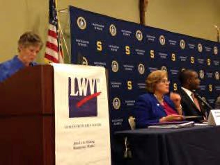 Moderator, candidates at forum. Podium banner reads LWV