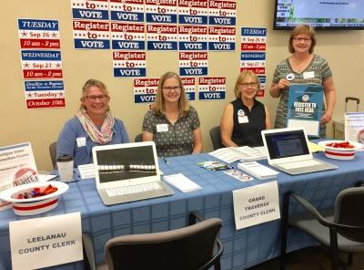 League members pose for a photo at registration table on National Voter Registration Day
