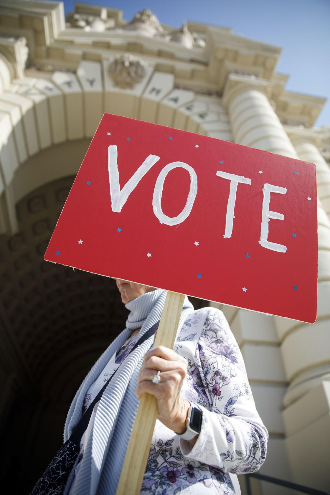 Woman Holding Red VOTE Sign Credit LWVUS