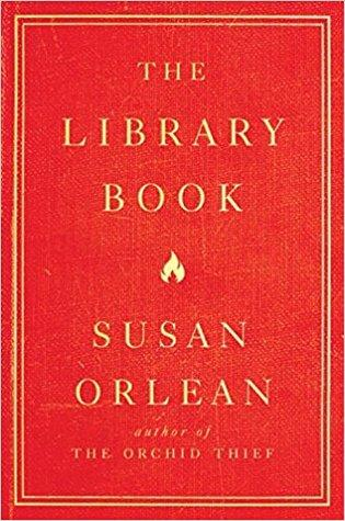 "An image of the cover of the book ""The Library Book"" by Susan Orlean. It is a red cover with ivory text and two close concentric rectangles around the text. It also reads, ""Author of The Orchid Thief."""