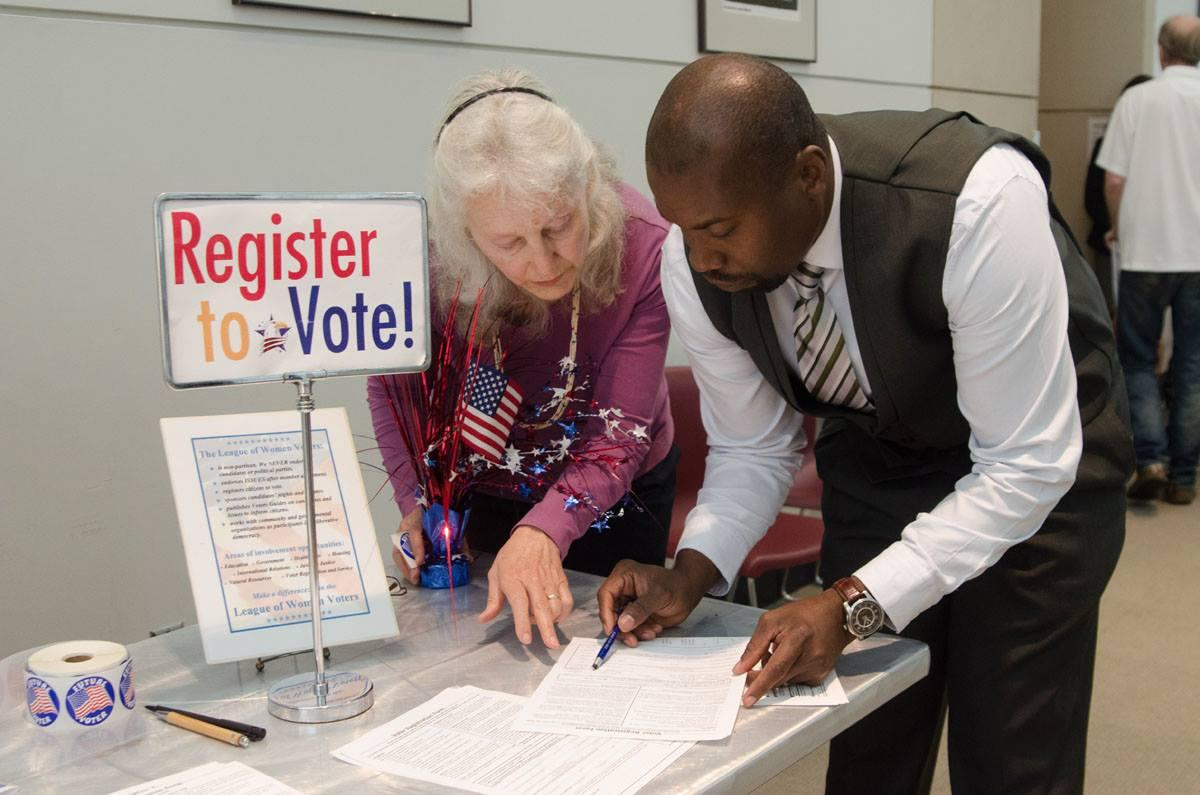 League member helps man fill out voter registration form