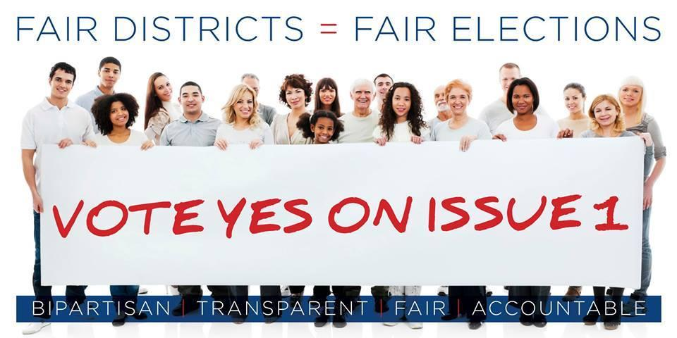 People holding Vote Yes on Issue 1 sign
