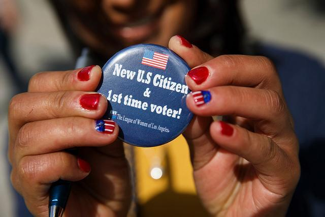 Hands holding a New Citizen First time voter button