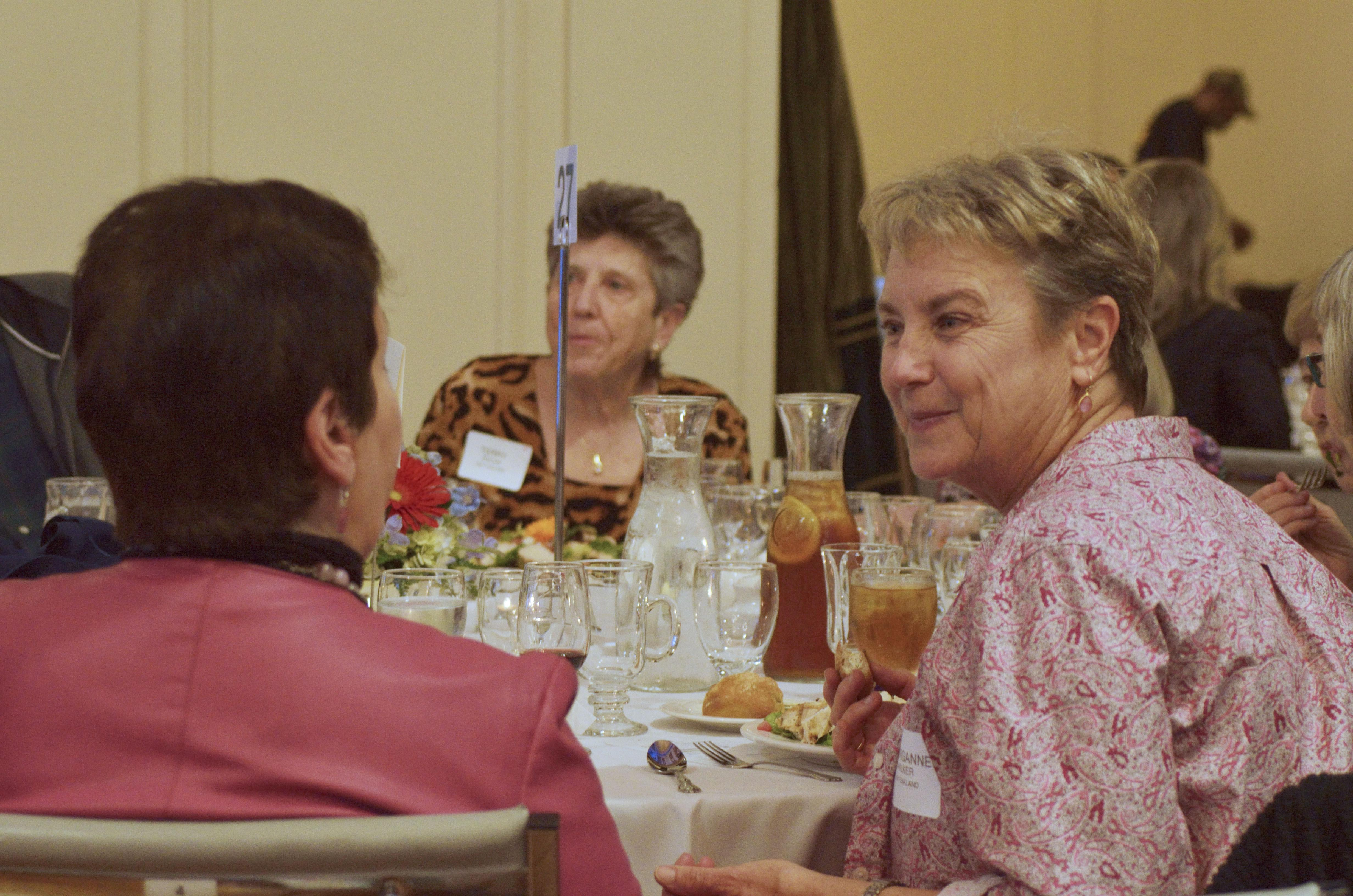 Photo of people chatting at a table at the 2018 Luncheon