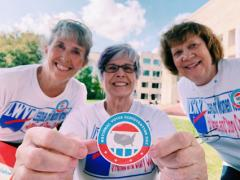 League members close-up, one extends arms holding National Voter Registration Day sticker