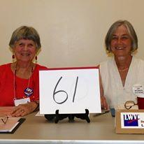 Two women at table with ballot measure number on placard