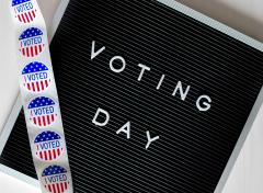"Voting Day letterboard with strip of ""I VOTED"" stickers draped over letterboard"