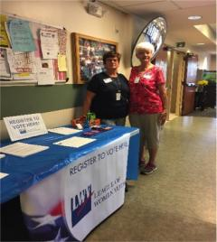 Two women standing by voter registration table