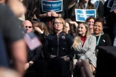 An image of former US Representative for Arizona Gabby Giffords sitting in a crowd at a political rally with a young woman sitting beside her.