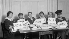 "Vintage LWV members holding ""Vote"" signs"