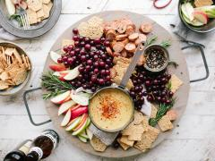 An image of a platter of crackers, fruit, and dips as for a party.